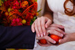 newlyweds hands rings on wedding bouquet