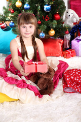 Beautiful little girl in holiday dress with gift in hands in
