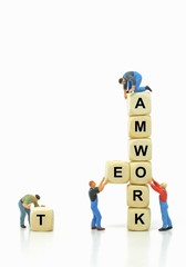Mini workmen in teamwork concept with copy space