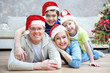 Portrait of happy family in Christmas hat at home