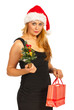 Woman holding Christmas tree and gift
