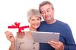 senioren mit tablet und geschenk