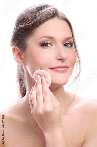 Attractive and happy woman cleaning her face