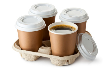 Four take-out coffee in holder. One cup is openend.