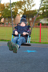 little boy on a swing at the park