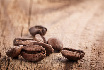 Coffee grains on grunge wooden background