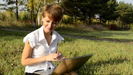 Business woman uses a laptop in autumn park