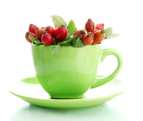 ripe hip roses with leaves in cup, isolated on white