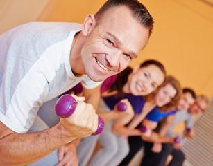 Mann im Fitnesscenter hebt Hanteln