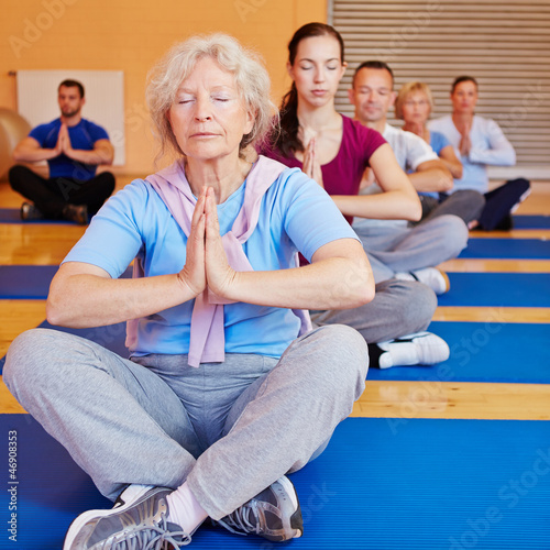 Seniorin macht Entspannungsübung im Fitnesscenter