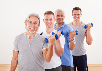 Row of men working with dumbbells