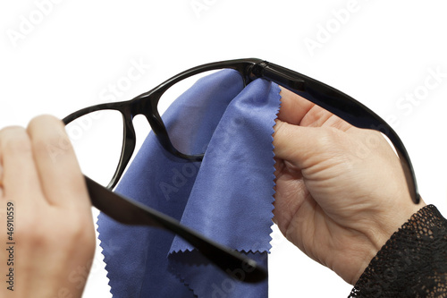 Woman trying to clean spectacles on a white background
