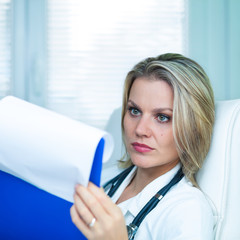 Pretty Young Female Doctor Is Studying Medical Results in Her Am