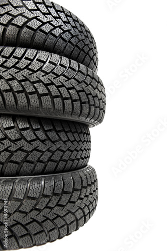 Stack of four car wheel winter tyres isolated