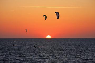 kitesurfers at sunset