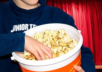 Kind mit einer Jumbo-Portion Popcorn im Kino