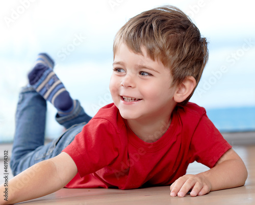 Three years old boy having fun on the floor