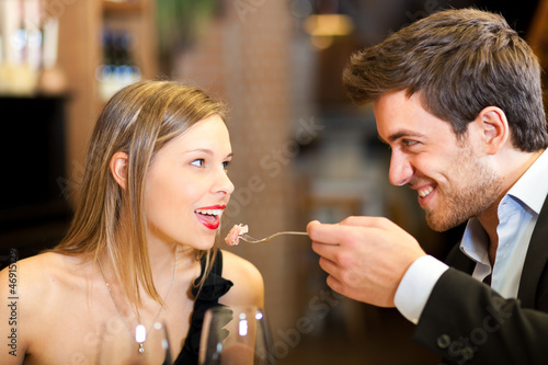 Romantic couple having dinner, man feeding woman