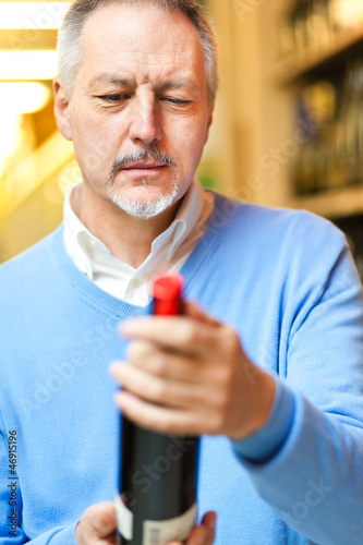 Man looking at a bottle of wine in a shop