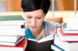 Reading book female student surrounded with piles of books