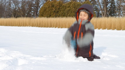 Little boy throws snow up in winter