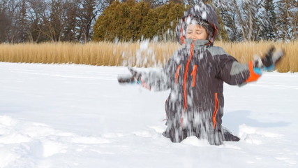 Little boy throws snow up in winter. Slow motion.
