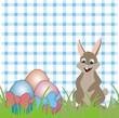 Osterhase mit Eiern auf karierter Decke