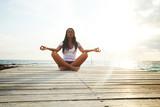 Yoga woman meditating near sea