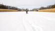 Little boy walking across white snow field with red sled