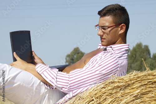boy with computers in the field of straw
