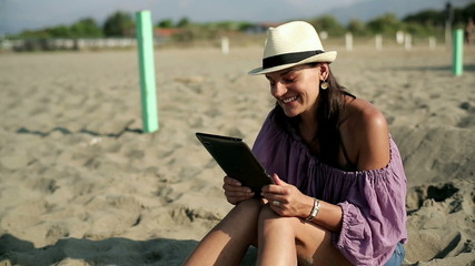 Young woman chatting on the beach with tablet computer