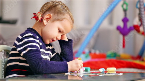 Little girl painting in concentration
