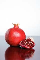 Studio shot of fresh ripe pomegranate whole and part with seeds.