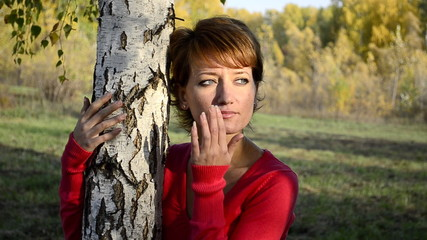 Sad young woman in autumn park hugging the birch