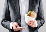 Man in suit sending sms while getting take away lunch