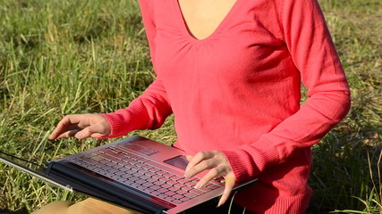 A student uses a laptop while sitting on the grass