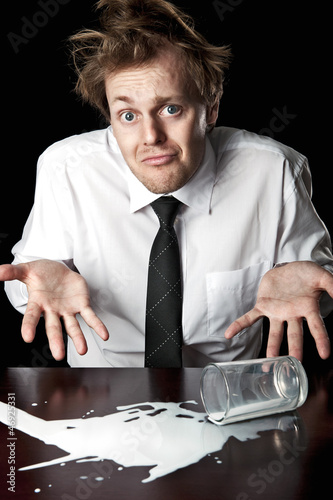 Helpless businessman with spilled milk on table