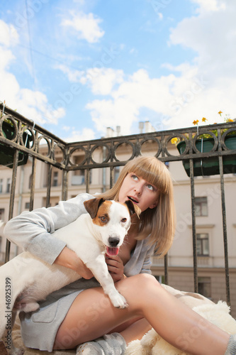 Beautiful pregnant woman with funny dog on the balcony