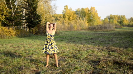 Young woman dancing in the autumn park