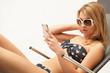 Schöne Blondine auf dem Liegestuhl mit Handy