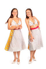 Two same women dressed in bikini and skirt smiles in studio