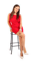 Beautiful woman dressed in red dress sits on stool in studio