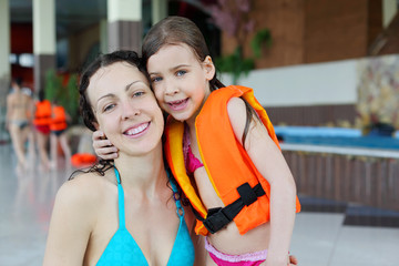 Happy wet mother and little daughter hug after swimming in pool.