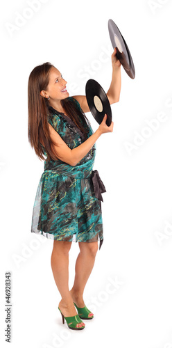 Beautiful woman dressed in dress holds record in studio on white