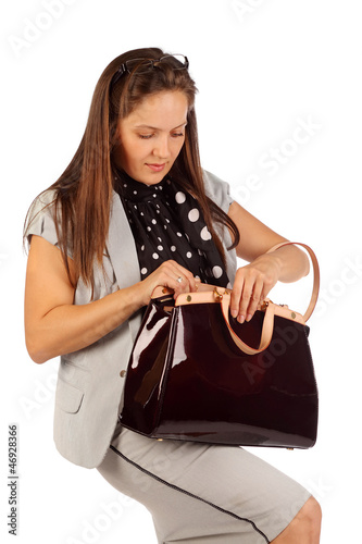 Business woman searches for something in big bag in studio