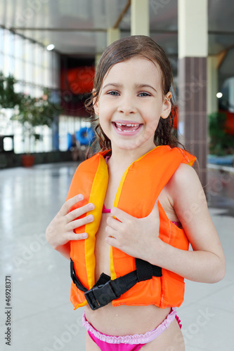 Little sorrowful girl wearing orange life-jacket laughs