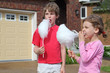 Little girl and boy eat cotton candy and look toward