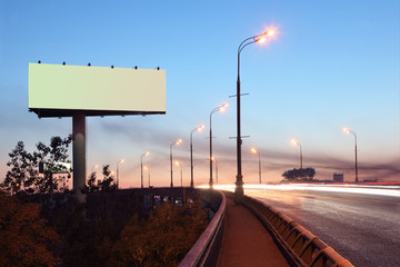 Road with lights and large blank billboard at evening in city.