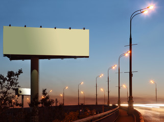 Road with lanterns and large blank billboard at evening in city.