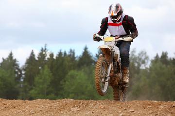 Motorcyclist wearing helmet on dirt bike jumps on muddy potholes